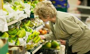 Woman choosing bananas in supermarket