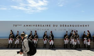 A photographer walks in front of the French republican guard in Ouistreham, before the ceremony of the D-day commemorations.
