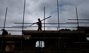 A builder works on new homes being built on a council housing estate in London