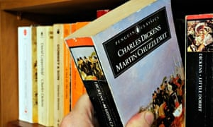 A hand taking Charles Dickens Martin Chuzzlewit  from a bookshelf