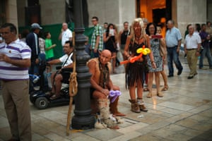 Street performers watch an anti-monarchy demonstration in Malaga, Spain.