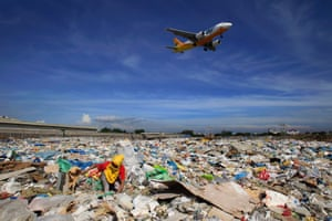 A plane flies over a person as they search for recyclables at a rubbish dump in Paranaque city, Philippines.