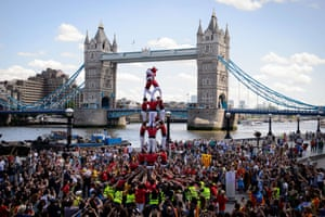 """A group of castellers create a Catalan Tower in front of Tower Bridge in London before unfurling a banner reading """"Catalans want to vote""""."""