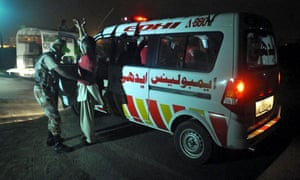 Pakistani Rangers check ambulance staff at the perimeter wall after suspected militants attacked Jinnah International Airport in Karachi.