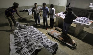 Volunteers look at dead bodies of people killed during an attack by unknown gunmen on Jinnah International Airport.