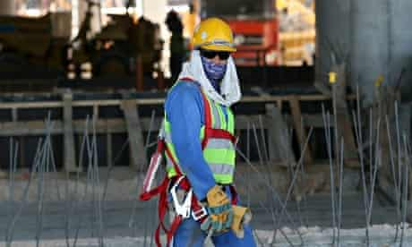 Worker in yellow helmet and dark glasses on construction site