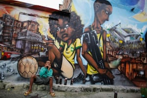 Ryan, 9, eats in front of graffiti painted by members of OPNI n the Vila Flavia of Sao Paulo