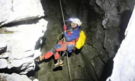 A rescuer enters a cave as part of the effort to lift the man stuck deep inside the rock system