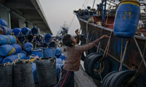 A young Cambodian migrant worker loads barrels at Songkhla