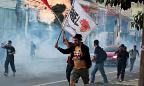 Demonstrators run from tear gas fired by police outside Ana Rosa subway station in Sao Paulo
