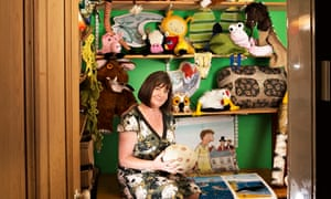Julia Donaldson sitting in a small room among shelves of toys and props