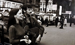 Julian Donaldson with long hair and her husband with a guitar on a Bristol street