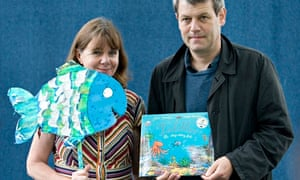 Julia Donaldson holding a paper fish and Axel Scheffler holding their book Tiddler