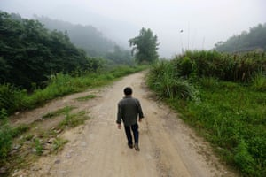 Sixty-one-year-old villager Xiong Dejun walks towards a bus station, on his way to get an X-ray examination for his lungs at a hospital in Heshan village, Shimen county, central China's Hunan Province