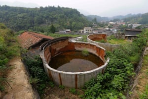 Two disused tanks are seen at a closed realgar mining plant at Heshan village, in Shimen county, central China's Hunan Province