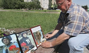 A Ukrainian man lights a candle in front of photos of killed Russian journalists in Donetsk