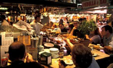 People eat at stall in Barcelona's Boqueria market
