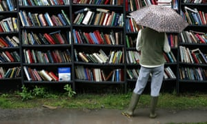 woman wearing wellies looks at books