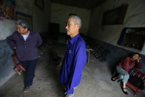 Gong Zhaoyuan (C), 69, who suffers from skin cancer stands next to his wife Wu Qunyao (L) and neighbour Wen Jin'e, who had cervical cancer, at his home at Heshan village, in Shimen county, central China's Hunan Province,