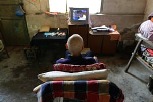 Qin Wenji, 82, who suffers from skin cancer, watches TV in his bedroom at Heshan village, in Shimen county, central China's Hunan Province,