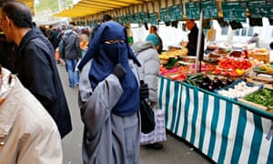 A woman wears a burqa at a market in Paris despite it being banned in France