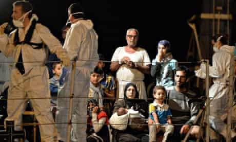 Migrants wait to disembark from the Italian navy ship Grecale