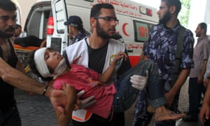 A man carries a Palestinian girl, who hospital officials said was wounded in an Israeli air strikegroup in the northern Gaza Strip.