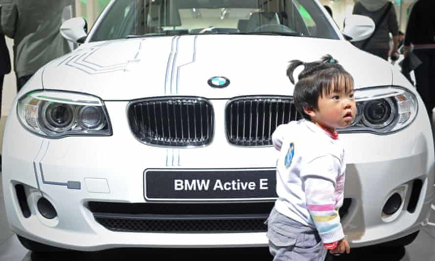 A Chinese child looks on next to the Active-E , an electric car made by German car manufacturer BMW, at the Shanghai Auto Show in Shanghai