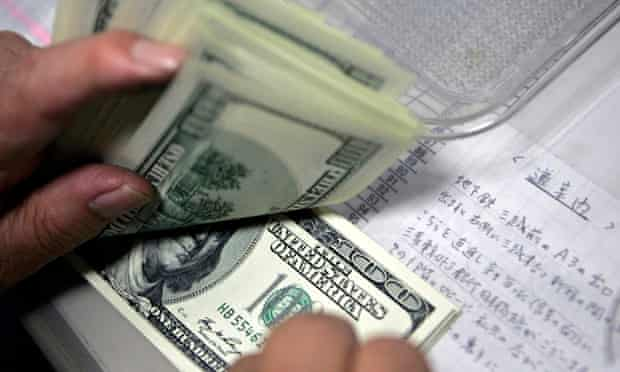 An employee counts U.S. dollars at a money exchange in Tokyo