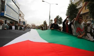 People hold a giant Palestinian flag as they demonstrate to denounce Israeli air strikes on the Gaza strip, in Sanaa July 10, 2014.