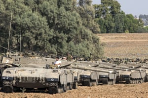Israeli soldiers rest on top of their Merkava tanks in an army deployment area near Israel's border with the Gaza Strip on July 10, 2014.