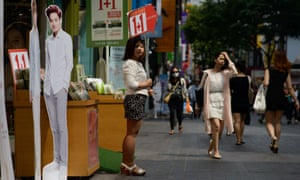 A shop assistant advertises a promotion outside a cosmetics shop next to cardboard cut-outs of popular entertainers, in central Seoul.