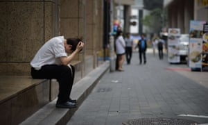 A restaurant worker sits on a street in the Myeongdong shopping area in Seoul.