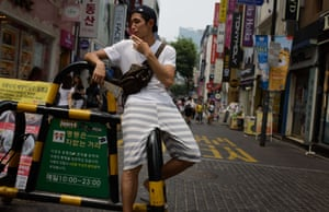 A local man pauses for a cigarette in the Myeongdong shopping district of Seoul.