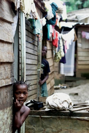 A young girl leans out of the doorway of her house in a slum neighbourhood of Malabo, capital of Equatorial Guinea, in 2002. (AP Photo/Christine Nesbitt)