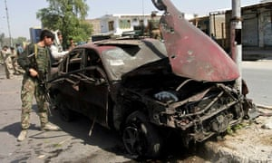 A member of the Afghan security force checks a car damaged in the Jalalabad blast