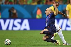 Brazil's midfielder Fernandinho hacks down Arjen Robben.