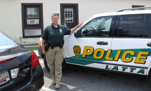 Latta police chief Crystal Moore stands beside her police SUV.