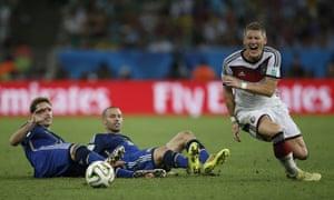 Bastian Schweinsteiger goes down under the double challenge of Lucas Biglia and Argentina's midfielder Javier Mascherano.