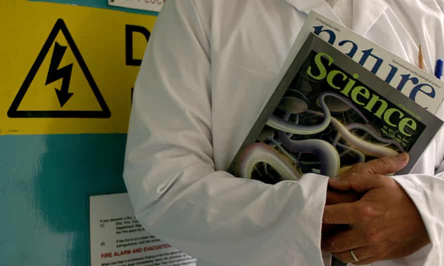 A scientist carrying the science journals Science and Nature