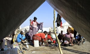South Sudanese refugees cook on an open fire at a camp