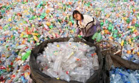 Chinese migrant workers sort through various materials at a recycling centre in Beijing