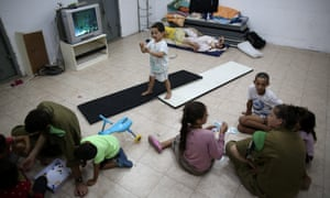Israeli soldiers play with children inside a public shelter in the southern city of Ashkelon, Israel.