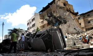 Palestinians inspect the buildings destroyed in air attacks staged by Israel army to hit the al-Raziq's house.