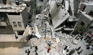 Palestinians look at the rubble of a destroyed house.