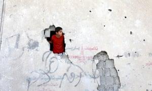 A Palestinian boy looks through a hole in a building hit by an Israeli air strike. gaza