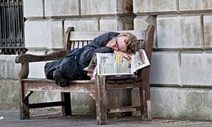 A homeless man asleep on a bench outside St Bartholomew's hospital, London