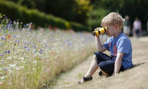 Child playing with binoculars in the gardens in July at Polesden Lacey, Surrey.