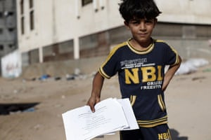 A Palestinian boy shows flyers dropped over Gaza City by the Israeli army urging residents to evacuate their home by 0500 GMT.