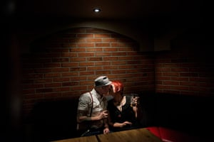 Weekend - Skinheads : man in hat with tattoos and girl with red hair kissing in dimly lit bar